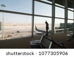 Small photo of AMMAN, JORDAN - MAY 3, 2017: Unidentified man looking at a plane from interior Luxury queen alia international airport.