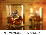Stock photo chilled whiskey glass with ice cubes 1077366362