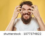 a man with a beard holds his...   Shutterstock . vector #1077374822