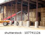 Farm Vehicle Lifting Bails Of...