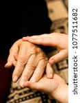 Small photo of Little child caressing the hand of grandmother, close-up photo. Family care, elderly and generation concept