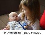 sister holding her newborn... | Shutterstock . vector #1077595292