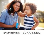 young mixed race mother and... | Shutterstock . vector #1077765302