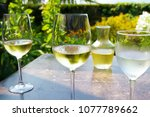 glasses of white wine at an... | Shutterstock . vector #1077789662