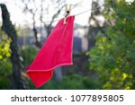 a red rag is dried on a rope... | Shutterstock . vector #1077895805