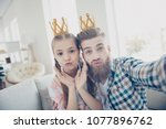 Small photo of Self portrait of funny trendy father and daughter having crowns on heads shooting selfie on front camera sending air kiss with pout lips spending free time indoor in house wearing checkered shirts