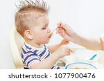 mom feeds her beautiful baby... | Shutterstock . vector #1077900476