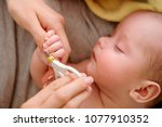 Small photo of Baby getting fingernails cut while sleeping by his mother with scissors. Nursing a child. How to successfully clip your baby's nails