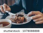 man in black eating cake in... | Shutterstock . vector #1078088888