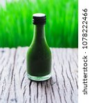 Small photo of Fresh wheatgrass in bottle on wooden table and blurry green background. Detox drinking. Healthcare juice concept.
