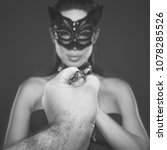 Small photo of Strong man hand holding submissive lover in mask on chain, bdsm concept, black and white