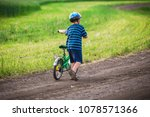 little boy walking uphill with... | Shutterstock . vector #1078571366