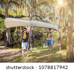 Small photo of Two Adventuresome men ready go canoeing on a tropical river as they carry their canoe into the water smiling and ready for fun time in the outdoors