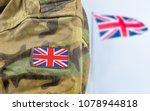 Military man posing in front of UK flag - stock photo
