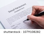 Stock photo close up of a human hand filling sexual harassment complaint form with pen 1079108282