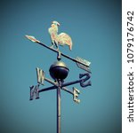 Small photo of weathervane also called weathercock with vintage effect and blue sky on background