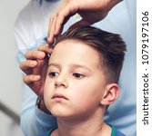 Small photo of Barber is making a hairstyle with hair gel to a boy in barbershop.