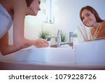 young woman washing her face... | Shutterstock . vector #1079228726