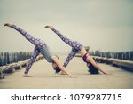 two woman playing yoga pose on... | Shutterstock . vector #1079287715
