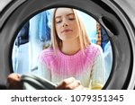 young woman doing laundry in...   Shutterstock . vector #1079351345