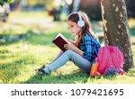 schoolgirl reading a book in... | Shutterstock . vector #1079421695