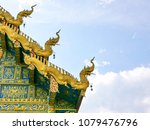 Small photo of Beautiful gloden blue Thai temple front roof against blue sky and fluffy white clouds - people's faith and belief motivated them to build stunning architecture through out our mankind history