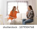 women arguing on sofa at home | Shutterstock . vector #1079504768