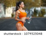 Young Fit Woman Drinking Water...