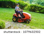 gardener driving a riding lawn... | Shutterstock . vector #1079632502