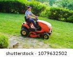 gardener driving a riding lawn... | Shutterstock . vector #1079632502