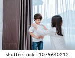 Small photo of Mother dressing up a son for beginner school lessen and first day at room to going kindergarten education, parent protection boy concept.