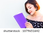 Small photo of Attractive beautiful woman feel happy when she read her favorite poem, novel book when she has free time that make her feel relaxed, happy. Read entertainment book make her relieve stressed from work