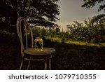 Stock photo fireflies inside a jar on an old chair outdoor 1079710355