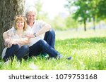 happy senior couple sitting on... | Shutterstock . vector #1079753168