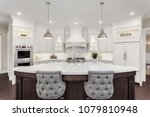 Stock photo beautiful kitchen in luxury home with large island refrigerator pendant lights double ovens 1079810948