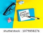 Small photo of Learn english - note at blue and yellow background with teachers glasses