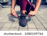 sporty person checking shoelaces | Shutterstock . vector #1080109766