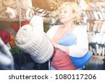 Small photo of Adult female buyer choosing colour plaids in the textile store
