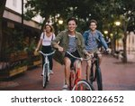 Three young people cycling down the street. Male and female friends on road with their bikes.