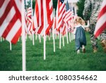 Patriotic Little girl walking with her dad in uniform holding 2 small American Flags in her hand - stock photo