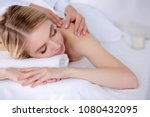 young woman lying on a massage... | Shutterstock . vector #1080432095