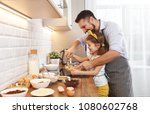 Small photo of happy family in kitchen. Father and child daughter knead dough and bake the biscuits together