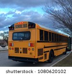 Small photo of Early Morning Layover for School Bus with Partially Cloudy Sky Background