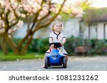 Stock photo cute little baby girl playing with blue small toy car in garden of home or nursery adorable 1081231262