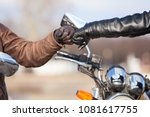 Small photo of Close up of bikers hands in leather gloves with repay a salutation