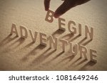 Small photo of ADVENTURE BEGIN wood word on compressed or corkboard with human's finger at B letter.