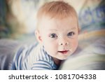 A Cute Blond Baby In White And...