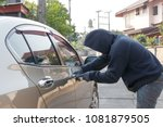 Male thief tries to steal a car. Car theft concept - stock photo