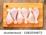 raw chicken legs on a cutting... | Shutterstock . vector #1082034872