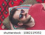 handsome hipster lying on rug... | Shutterstock . vector #1082119352